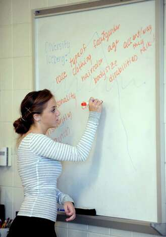 Trumbull High School peer leader Olivia DeRosa, 17, constructs a diversity iceberg, made up of things, seen and unseen, that students are sometimes ridiculed over, during a presentation on cyberbullying Friday, Oct. 7, 2011 at the school. Photo: Autumn Driscoll