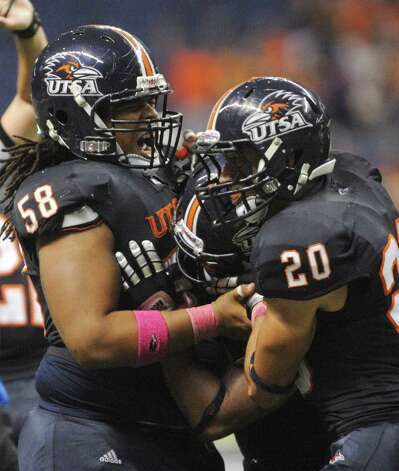Ferrington Macon (58) and Mauricio  Sanchez (20) of UTSA mob teammate Mark Waters after he intercepted a Southern Alabama pass in the end zone during college football action at the Alamodome on Saturday, Oct. 8, 2011. BILLY CALZADA / gcalzada@express-news.net