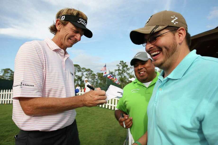 GOOD TIMES: Tournament leader Brad Faxon, left, has a smile and an autograph for fans Julian Almaguer, right, and Jaime Aleman after finishing his round of 65 on Saturday. Photo: Eric Christian Smith