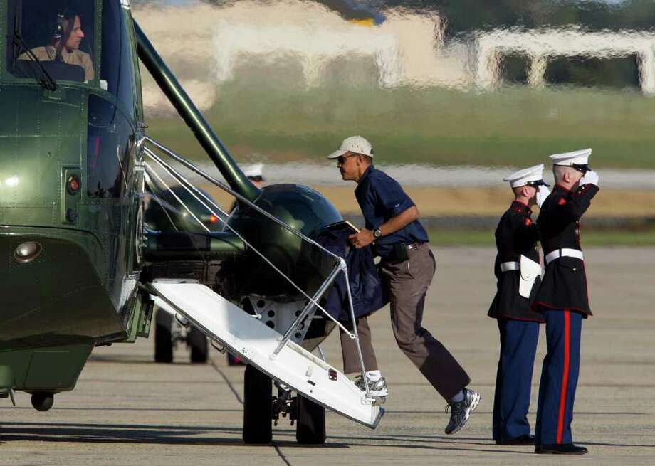 President Barack Obama boards Marine One, Saturday, Oct. 8, 2011, in Andrews Air Force Base, Md., en route to Camp David.  (AP Photo/Carolyn Kaster) Photo: Carolyn Kaster