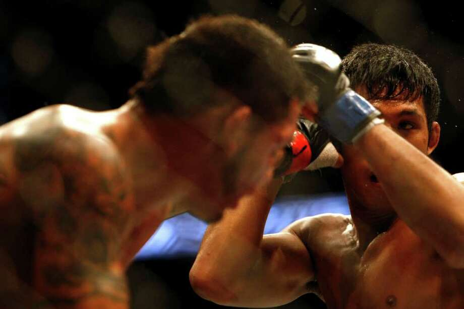 """Nam Phan, right, fights Leonard Garcia in a featherweight bout where Phan won in three rounds before the UFC 136 lightweight title bout with Gray """"The Bully"""" Maynard and Frankie """"The Answer""""  Edgar at Toyota Center Saturday, Oct. 8, 2011, in Houston.  Before tonight Edgar's MMA record was 13-1-1 and 8-1-1 in UFC. Maynards MMA record was 11-0-1 and 8-0-1 in UFC Photo: Johnny Hanson, Houston Chronicle / © 2011 Houston Chronicle"""