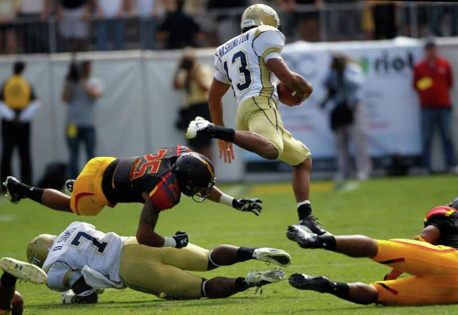 JOHN BAZEMORE : ASSOCIATED PRESS FLIGHT OF THE YELLOW JACKET: Everyone has a leg up as Georgia Tech's Tevin Washington takes off in the third quarter with the help of a block by David Sims (7) on Maryland's Alex Twine. Washington rushed for 120 yards and two touchdowns as the No. 13 Yellow Jackets improved to 6-0 with a 21-16 victory. Photo: John Bazemore / AP