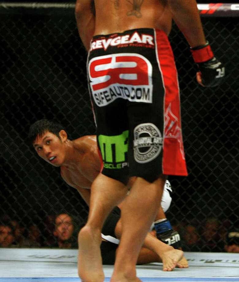 """Nam Phan, down, fights Leonard Garcia in a featherweight bout where Phan won in three rounds before the UFC 136 lightweight title bout with Gray """"The Bully"""" Maynard and Frankie """"The Answer""""  Edgar at Toyota Center Saturday, Oct. 8, 2011, in Houston.  Before tonight Edgar's MMA record was 13-1-1 and 8-1-1 in UFC. Maynards MMA record was 11-0-1 and 8-0-1 in UFC Photo: Johnny Hanson, Houston Chronicle / © 2011 Houston Chronicle"""