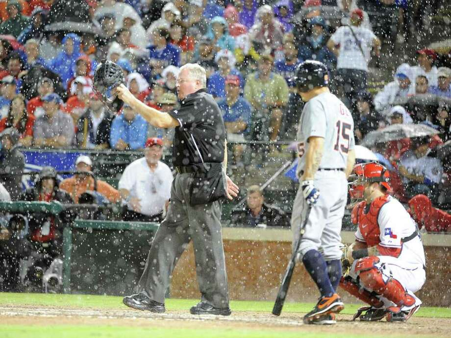 MARK J. TERRILL: ASSOCIATED PRESS IT TOOK A WHILE: Manager Ron Washington hugs relief pitcher Neftali Feliz (right photo) after the Rangers finally defeat the Tigers 3-2 at Arlington on a night in which home-plate umpire Tim Welke (left photo) called two rain delays in the top of the fifth inning. Photo: Max Faulkner / Fort Worth Star-Telegram