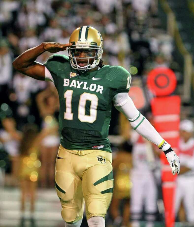 Baylor quarterback Robert Griffin III salutes after throwing a touchdown pass to wide receiver Kendall Wright in the first half of an NCAA college football game, Saturday, Oct. 8, 2011, in Waco, Texas. (AP Photo/Waco Tribune-Herald, Jerry Larson) Photo: Jerry Larson / AP2011