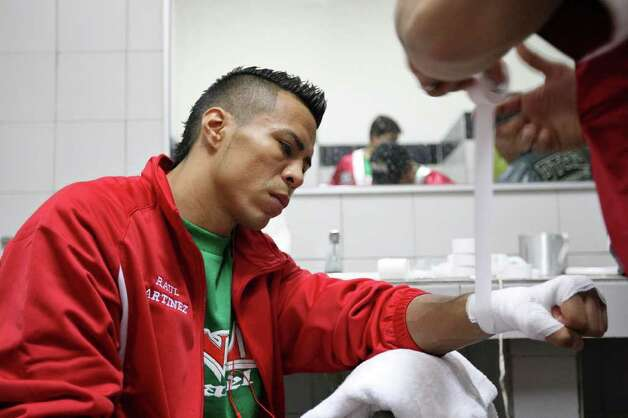FOR SPORTS - Raul Martinez has his hands wrapped by trainer Jesus Chavez before his IBF super flyweight title fight against Rodrigo Guerrero at the Auditorio Municipal in Tijuana, Baja California, Mexico Saturday Oct. 8, 2011.  (PHOTO BY EDWARD A. ORNELAS/eaornelas@express-news.net) Photo: EDWARD A. ORNELAS, SAN ANTONIO EXPRESS-NEWS / © SAN ANTONIO EXPRESS-NEWS (NFS)
