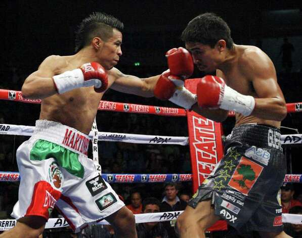 FOR SPORTS - Raul Martinez (left) and  Rodrigo Guerrero exchange punches during first round action of their IBF super flyweight title fight held at the Auditorio Municipal in Tijuana, Baja California, Mexico Saturday Oct. 8, 2011.  (PHOTO BY EDWARD A. ORNELAS/eaornelas@express-news.net) Photo: EDWARD A. ORNELAS, SAN ANTONIO EXPRESS-NEWS / © SAN ANTONIO EXPRESS-NEWS (NFS)