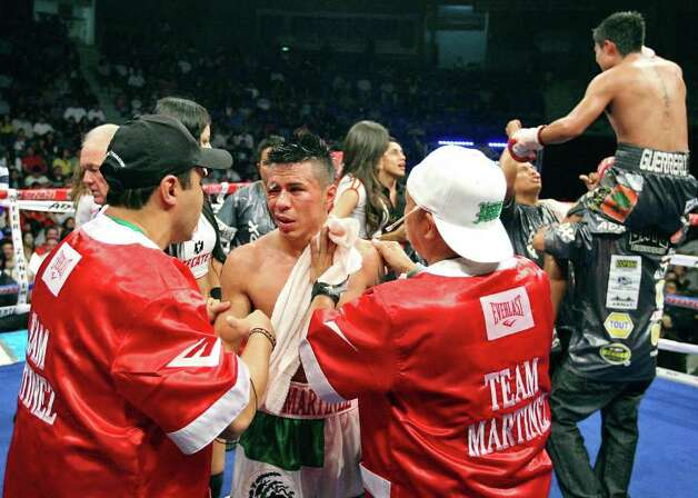 FOR SPORTS - Raul Martinez (center) talks with trainer Jesus Chavez (left) and  cutman Joe Villanueva after his IBF super flyweight title fight with Rodrigo Guerrero held at the Auditorio Municipal in Tijuana, Baja California, Mexico Saturday Oct. 8, 2011. Guerrero won by a technical decision after the fight was stopped after the sixth round.  (PHOTO BY EDWARD A. ORNELAS/eaornelas@express-news.net) Photo: EDWARD A. ORNELAS, SAN ANTONIO EXPRESS-NEWS / © SAN ANTONIO EXPRESS-NEWS (NFS)
