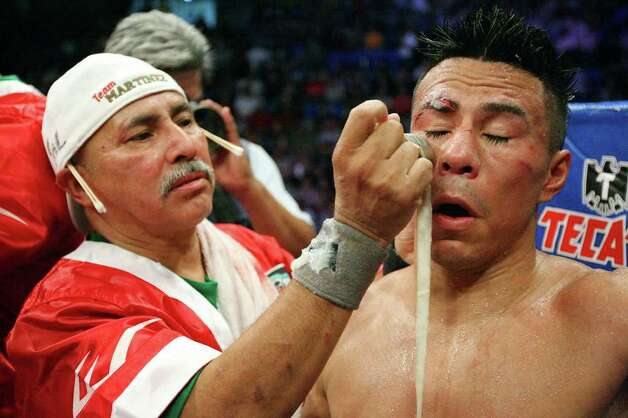 FOR SPORTS - Cutman Joe Villanueva works on Raul Martinez after his IBF super flyweight title fight with Rodrigo Guerrero held at the Auditorio Municipal in Tijuana, Baja California, Mexico Saturday Oct. 8, 2011. The fight was stopped after the sixth round. Guerrero won by a technical decision. (PHOTO BY EDWARD A. ORNELAS/eaornelas@express-news.net) Photo: EDWARD A. ORNELAS, SAN ANTONIO EXPRESS-NEWS / © SAN ANTONIO EXPRESS-NEWS (NFS)