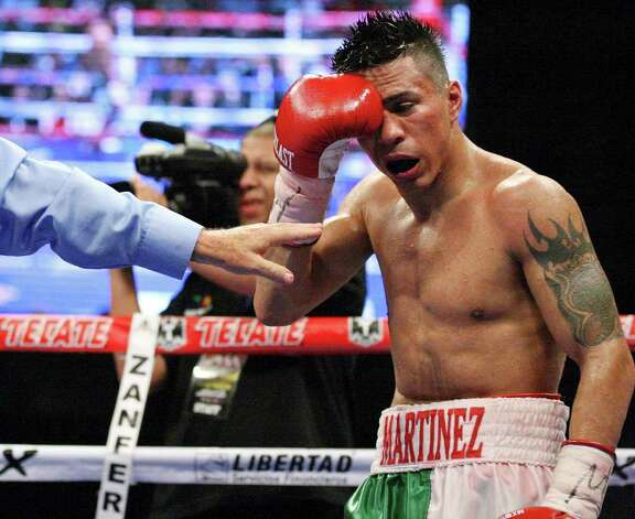 FOR SPORTS -  Raul Martinez holds his right eye during the fifth round of his IBF super flyweight title fight with Rodrigo Guerrero held at the Auditorio Municipal in Tijuana, Baja California, Mexico Saturday Oct. 8, 2011. The fight was stopped after the sixth round. Guerrero won by a technical decision. (PHOTO BY EDWARD A. ORNELAS/eaornelas@express-news.net) Photo: EDWARD A. ORNELAS, SAN ANTONIO EXPRESS-NEWS / © SAN ANTONIO EXPRESS-NEWS (NFS)