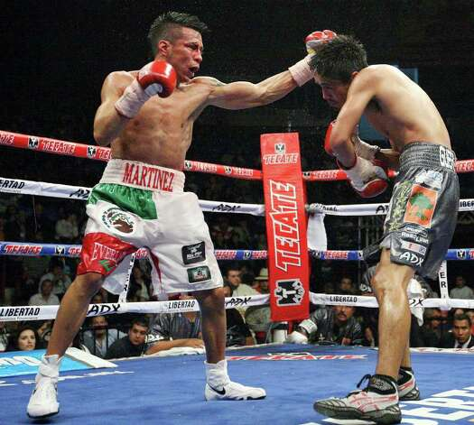 FOR SPORTS - Raul Martinez (left) hits Rodrigo Guerrero with a left during the sixth round of their IBF super flyweight title fight held at the Auditorio Municipal in Tijuana, Baja California, Mexico Saturday Oct. 8, 2011. Guerrero won by a technical decision after the fight was stopped after the sixth round.  (PHOTO BY EDWARD A. ORNELAS/eaornelas@express-news.net) Photo: EDWARD A. ORNELAS, SAN ANTONIO EXPRESS-NEWS / © SAN ANTONIO EXPRESS-NEWS (NFS)