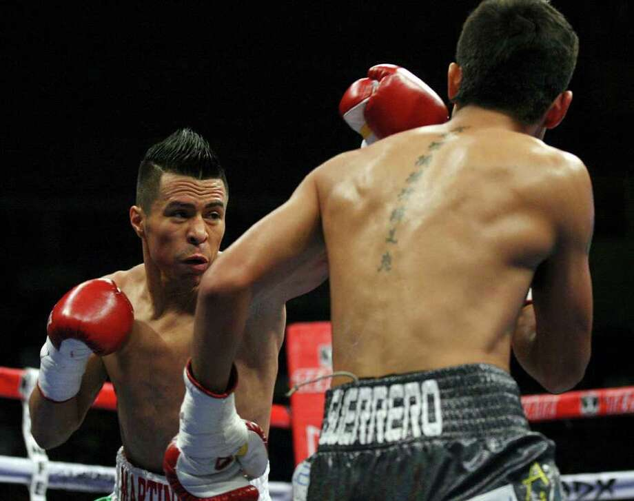 "San Antonio's Raul Martinez, throwing a left against Rodrigo Guerrero in a bout late last year, could be sidelined ""four to six months"" by biceps and rotator cuff injuries suffered recently against Juan Jimenez in Mexico. EDWARD A. ORNELAS/eaornelas@express-news.net Photo: EDWARD A. ORNELAS, SAN ANTONIO EXPRESS-NEWS / © SAN ANTONIO EXPRESS-NEWS (NFS)"