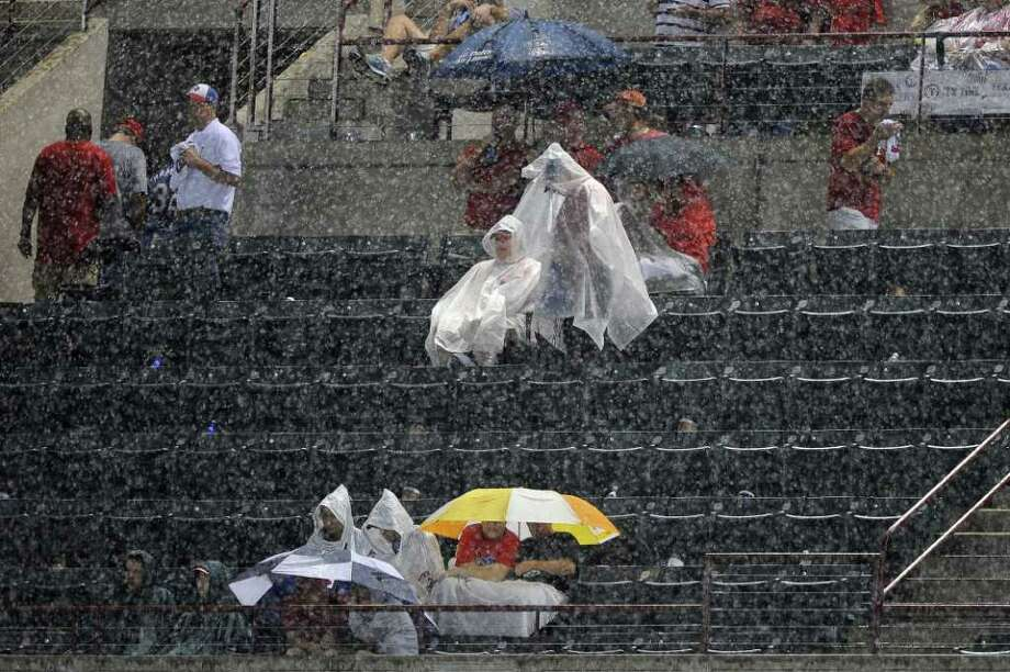 ARLINGTON, TX - OCTOBER 08:  Fans sit in the stands during a rain delay in Game One of the American League Championship Series between the Detroit Tigers and the Texas Rangers at Rangers Ballpark in Arlington on October 8, 2011 in Arlington, Texas. Photo: Kevork Djansezian, Getty / 2011 Getty Images