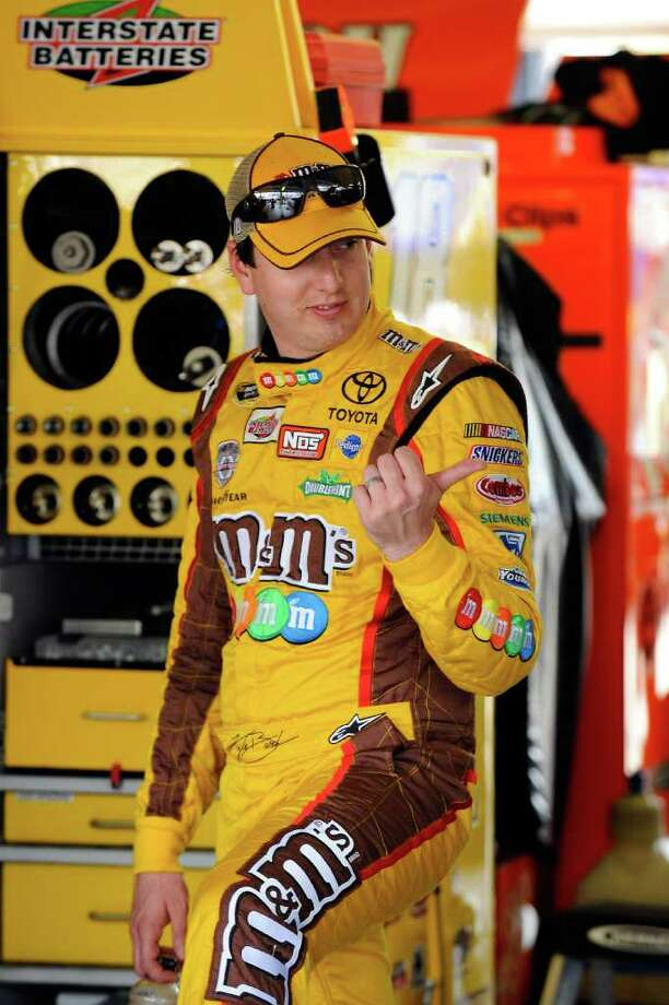 KANSAS CITY, KS - OCTOBER 08:  Kyle Busch, driver of the #18 M&M's Toyota, gestures in the garage area during practice for the NASCAR Sprint Cup Series Hollywood Casino 400 at Kansas Speedway on October 8, 2011 in Kansas City, Kansas.  (Photo by Jason Smith/Getty Images for NASCAR) Photo: Jason Smith