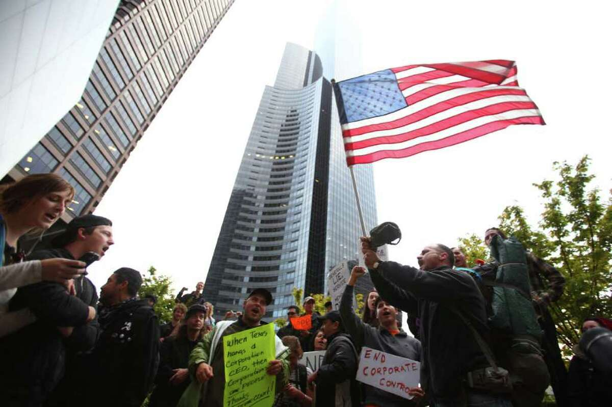 Chris Beiter, right, leads protesters in singing the Star Spangled Banner as Occupy Seattle protesters take to the streets of downtown Seattle during the second week of the local protest held in solidarity with the Occupy Wall Street protest in New York City. The marchers gathered at Bank of America Fifth Avenue Plaza and for a short time occupied a downtown intersection.