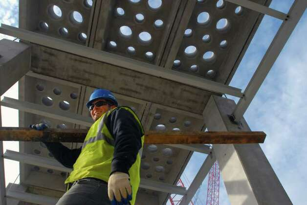 "A construction workers walks underneath pre cast ""waffle"" slabs that will be part of the floor of the clean room at the GLOBALFOUNDRIES Fab 2 Module 1 site chip fabrication plant under construction at the Luther Forest Technology Campus in Malta, NY on  Wednesday December 2, 2009. The holes in the slabs allow equipment and utilities to access the clean room. The floor will contain 924 of the 8 foot by 24 foot slabs, each weighing 48, 000 pounds. (according to M + W Zander) (Philip Kamrass /  Times Union) Photo: PHILIP KAMRASS / 00006649A"