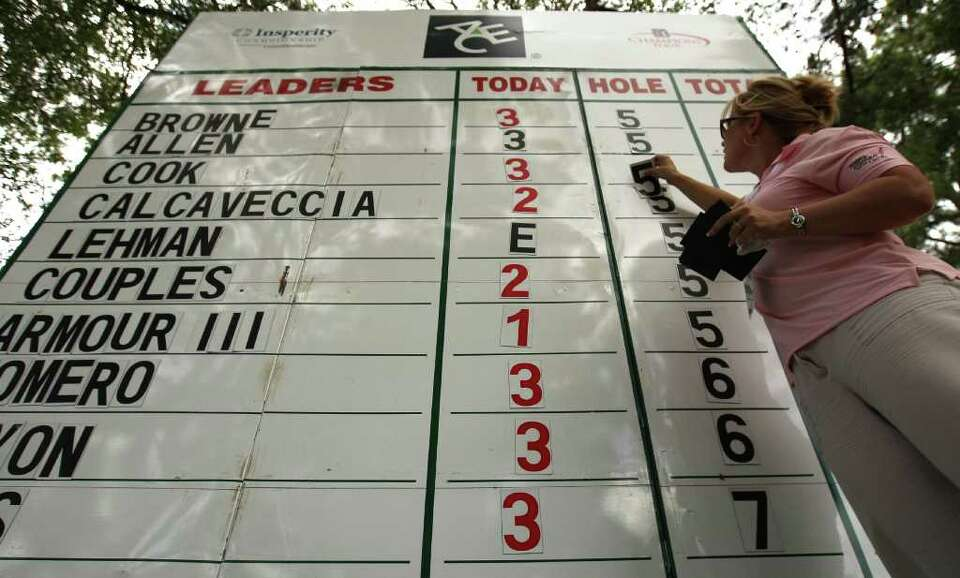 Tournament scorekeeper Jackie Knott adjusts the scoreboard between the Nos. 5 & 6 holes during the s
