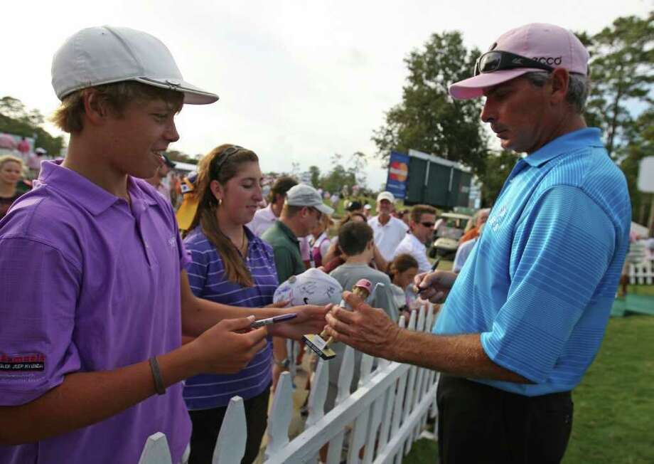 Fred Couples (right) signs a bobblehead doll of his likeness for fan Dalton Joyce after the second round of the Insperity Classic, Saturday, October 8, 2011 at the Tournament Course in The Woodlands, TX. Photo: Eric Christian Smith, For The Chronicle