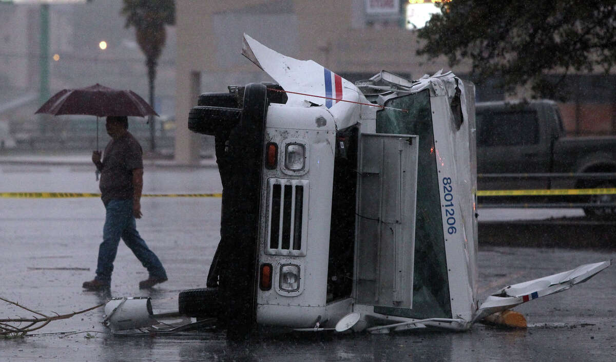 A pedestrian walks by a postal truck that was turned on its side by high winds that swept through San Antonio early Sunday morning. Several other trucks were damaged at the Valley Hi branch of the U.S. Post Office near Loop 410 and Valley Hi.