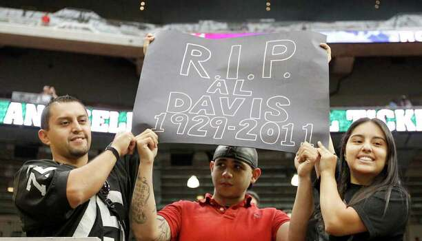 Oakland Raiders fans Mando Blancas, left, Luis Gonzales, center, and Jackie Blancas, Mando's sister, honor Raiders long time owner Al Davis, who passed away Friday, before a NFL football game against the Houston Texans at Reliant Stadium, Sunday, Oct. 9, 2011, in Houston. Photo: Karen Warren, Houston Chronicle / © 2011 Houston Chronicle