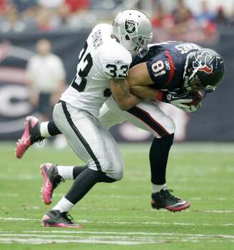 Oakland Raiders strong safety Tyvon Branch (33) tackles Houston Texans tight end Owen Daniels (81) during the first quarter of an NFL football game at Reliant Stadium on Sunday, Oct. 9, 2011, in Houston. Photo: Brett Coomer, Houston Chronicle / © 2011  Houston Chronicle