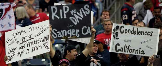 Oakland Raiders fans hold up signs in honor of Oakland Raiders owner Al Davis, who died Saturday morning at the start of an NFL football game at Reliant Stadium on Sunday, Oct. 9, 2011, in Houston. Photo: Brett Coomer, Houston Chronicle / © 2011  Houston Chronicle