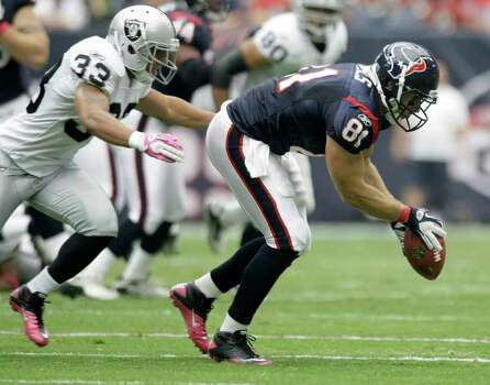 Houston Texans tight end Owen Daniels (81) manages to hold on to the ball for a catch as Oakland Raiders strong safety Tyvon Branch (33) defends during the first quarter of an NFL football game at Reliant Stadium on Sunday, Oct. 9, 2011, in Houston. Photo: Brett Coomer, Houston Chronicle / © 2011  Houston Chronicle