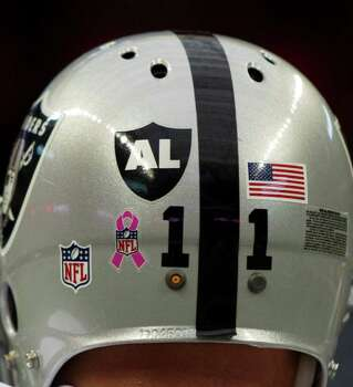 Oakland Raiders kicker Sebastian Janikowski (11) wears a decal on his helmet honoring Oakland Raiders owner Al Davis, who died early Saturday morning, before an NFL football game against the Houston Texans at Reliant Stadium on Sunday, Oct. 9, 2011, in Houston. Photo: Brett Coomer, Houston Chronicle / © 2011  Houston Chronicle