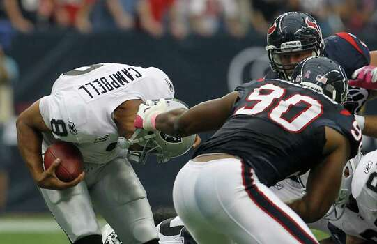 Oakland Raiders quarterback Jason Campbell (8) has his helmet pulled by Houston Texans outside linebacker Mario Williams (90) in the first quarter of an NFL football game at Reliant Stadium, Sunday, Oct. 9, 2011, in Houston. Photo: Karen Warren, Houston Chronicle / © 2011 Houston Chronicle