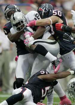 Oakland Raiders running back Taiwan Jones (22) tries to step over the Houston Texans defense for extra yards during the first quarter of an NFL football game at Reliant Stadium on Sunday, Oct. 9, 2011, in Houston. Photo: Brett Coomer, Houston Chronicle / © 2011  Houston Chronicle