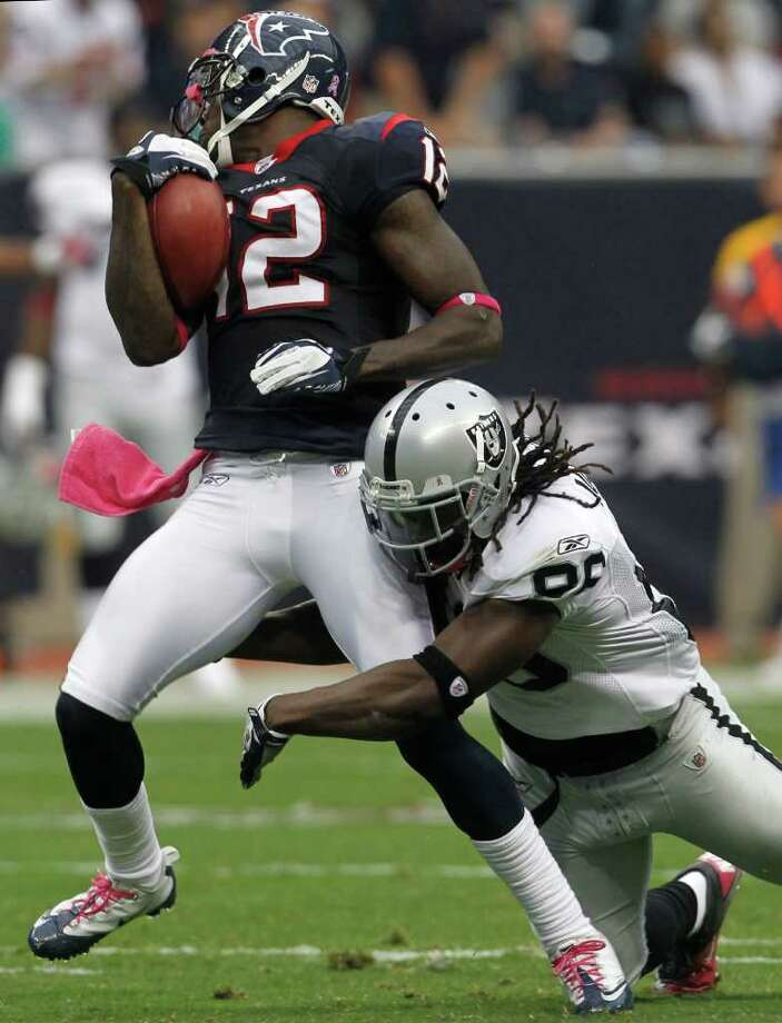 Houston Texans wide receiver Jacoby Jones (12) tries to spin away from Oakland Raiders special teams player David Ausberry (86) on a kick off during the first quarter of an NFL football game at Reliant Stadium, Sunday, Oct. 9, 2011, in Houston. Photo: Karen Warren, Houston Chronicle / © 2011 Houston Chronicle