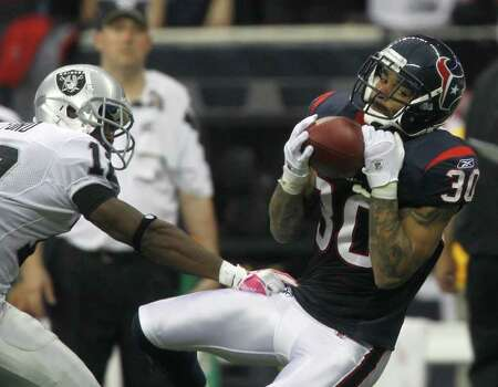Houston Texans cornerback Jason Allen (30) intercepts a ball intended for Oakland Raiders wide receiver Jacoby Ford (12) during the second quarter of an NFL football game at Reliant Stadium, Sunday, Oct. 9, 2011, in Houston. Photo: Karen Warren, Houston Chronicle / © 2011 Houston Chronicle