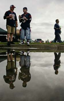 Mark Perez, left, of Spring, and Lance Tarin, of Houston tail gate by a rare rain puddle before a NFL football game between the Houston Texans and Oakland Raiders at Reliant Stadium on Sunday, Oct. 9, 2011, in Houston. Photo: Nick De La Torre, Houston Chronicle / © 2011  Houston Chronicle