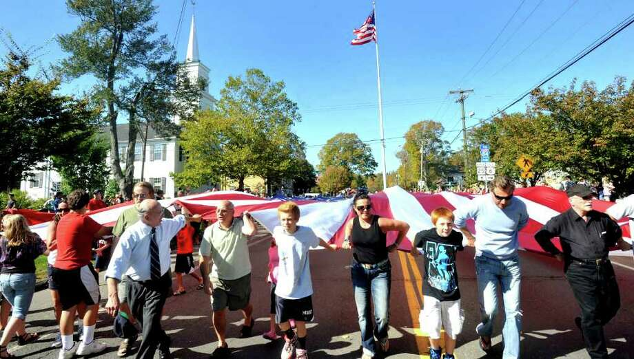 Parade goers, including the Matijevic family of Newtown, with Ellis, 12, left center, Corie, center, Matthew, 12, right center, and John, carry a giant World War II flag from the flagpole at the start of the 2011 Newtown Columbus Day Parade Sunday, Oct. 9. Photo: Michael Duffy / The News-Times