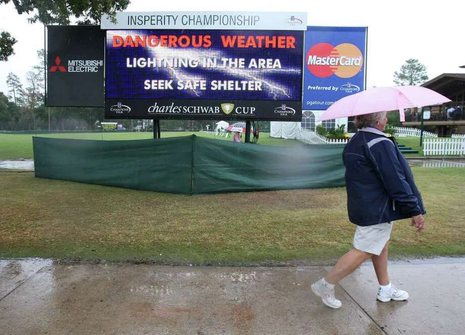 Volunteer Sharon Heuer walks past a scoreboard warning of dangerous weather during a rain delay at the final round of the Insperity Classic, Sunday, October 9, 2011 at the Tournament Course in The Woodlands, TX. The final round was eventually cancelled, and Brad Faxon was the winner at ten-under-par. Photo: Eric Christian Smith, For The Chronicle