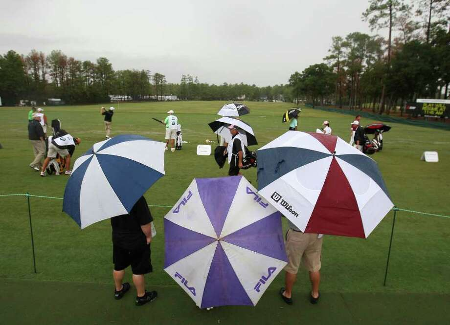 Patrons watch contestants warm up on the practice tee following a 1 hour 45 minute rain delay during the final round of the Insperity Classic, Sunday, October 9, 2011 at the Tournament Course in The Woodlands, TX. Play resumed, but was again delayed by heavier rain, and the final round was cancelled leaving Brad Faxon the winner at ten-under-par. Photo: Eric Christian Smith, For The Chronicle