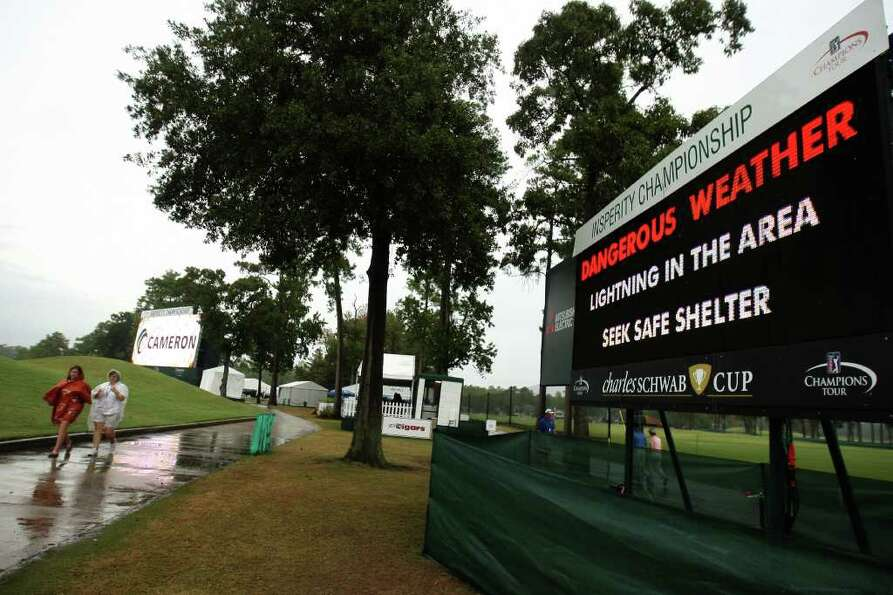 Patrons walk past a scoreboard warning of dangerous weather during a rain delay at the final round o