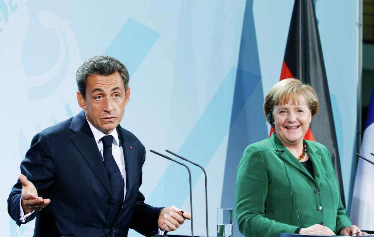Nicolas Sarkozy, France's president, and Angela Merkel, Germany's chancellor, react during a news conference at the Federal Chancellery in Berlin, Germany, on Sunday, Oct. 9, 2011. Merkel said European leaders will do