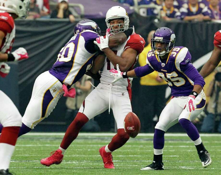 Minnesota Vikings linebacker Erin Henderson, left, and cornerback Marcus Sherels, right, break up a pass intended for Arizona Cardinals wide receiver Larry Fitzgerald, center, during the first half of an NFL football game on Sunday, Oct. 9, 2011, in Minneapolis. (AP Photo/Genevieve Ross) Photo: Genevieve Ross / AP