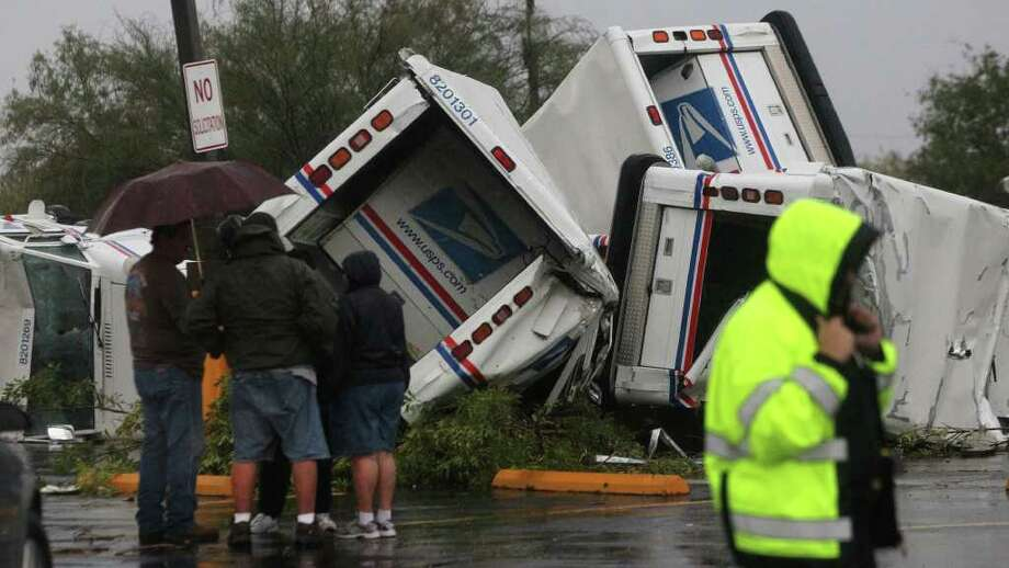 JOHN DAVENPORT : SAN ANTONIO EXPRESS-NEWS TWISTED METAL: U.S. Postal Service trucks at the Valley Hi branch in San Antonio were tossed around overnight by a tornado. The National Weather Service said a twister swept through the area about 1:20 a.m. Sunday. Photo: JOHN DAVENPORT / SAN ANTONIO EXPRESS-NEWS (Photo can be sold to the public)