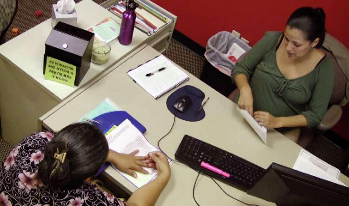 In this Oct. 6, 2011 photo taken from video, Jazmin Rivera, right, a case manager with the Hispanic Interest Coalition of Alabama, works with an unidentified immigrant in her office in Birmingham, Ala. Parents living in the country illegally are scared of deportation under Alabama's new immigration law, and Rivera has helped many with paperwork to provide care for their children in case the parents are arrested. (AP Photo/Jay Reeves)