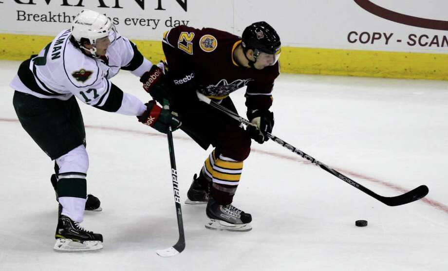 Houston Aeros Casey Wellman, left, and Chicago Wolves Antoine Roussel, right, battle for the puck during the first period of AHL game at Toyota Center, Sunday, Oct. 9, 2011, in Houston. Photo: Melissa Phillip, Houston Chronicle / © 2011 Houston Chronicle
