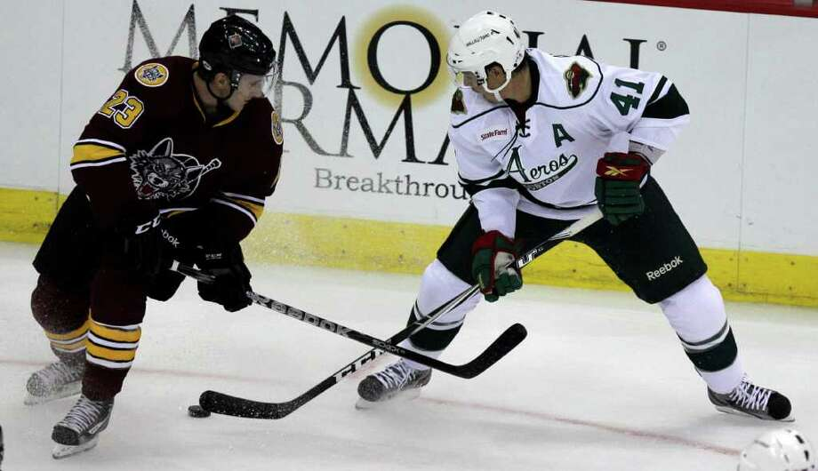 Chicago Wolves Bill Sweatt, left, and Houston Aeros Jed Ortmeyer battle for the puck during the first period of AHL game at Toyota Center, Sunday, Oct. 9, 2011, in Houston. Photo: Melissa Phillip, Houston Chronicle / © 2011 Houston Chronicle