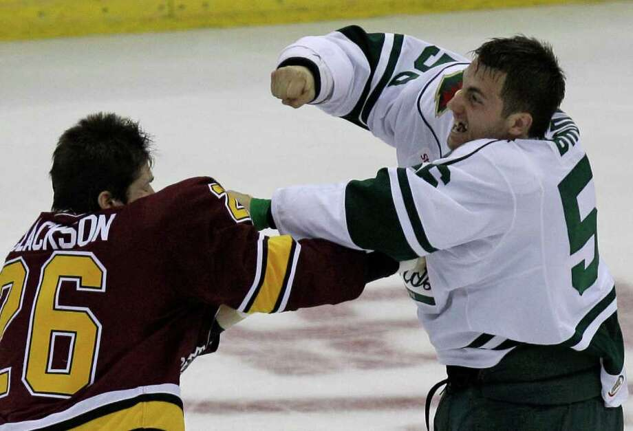 Chicago Wolves Mark Clackson, left, and Houston Aeros Joel Broda, right, fight during the second period of AHL game at Toyota Center, Sunday, Oct. 9, 2011, in Houston. Both received a five minute major penalty for fighting. Photo: Melissa Phillip, Houston Chronicle / © 2011 Houston Chronicle
