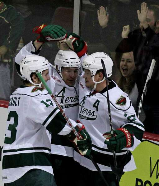Houston Aeros Kris Foucault, left, Jed Ortmeyer, center, and Warren Peters, right, celebrate goal sc