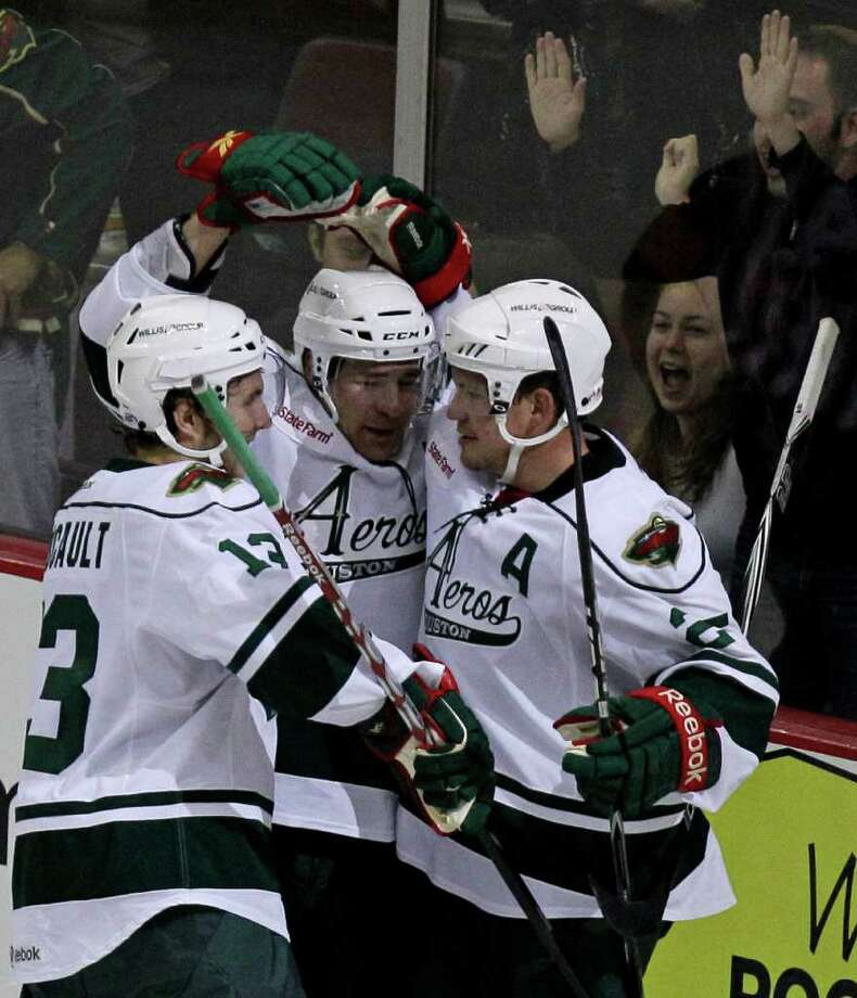 Houston Aeros Kris Foucault, left, Jed Ortmeyer, center, and Warren Peters, right, celebrate goal scored by Ortmeyer against the Chicago Wolves during the second period of AHL game at Toyota Center, Sunday, Oct. 9, 2011, in Houston. Both Foucault and Peters assisted on the goal. Photo: Melissa Phillip, Houston Chronicle / © 2011 Houston Chronicle
