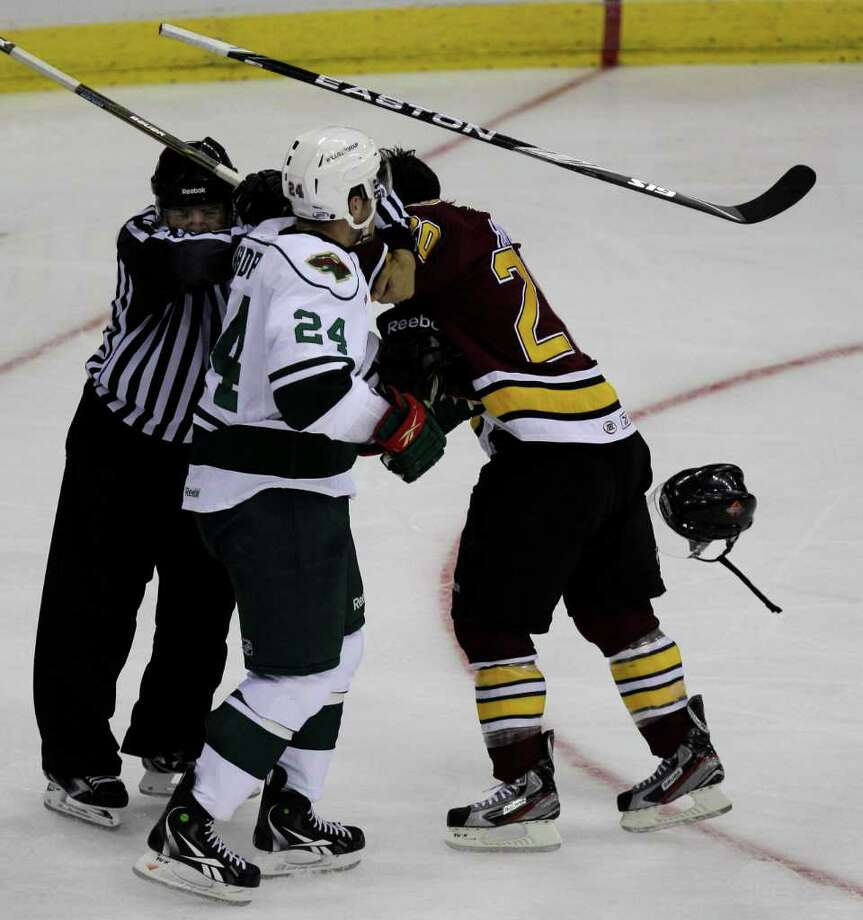 Equipment is sent flying as Houston Aeros Jordan Hendry, left, and and Chicago Wolves Darren Archibald, right,  fight during the second period of AHL game at Toyota Center, Sunday, Oct. 9, 2011, in Houston. Both received two minutes for roughing penalty. Photo: Melissa Phillip, Houston Chronicle / © 2011 Houston Chronicle