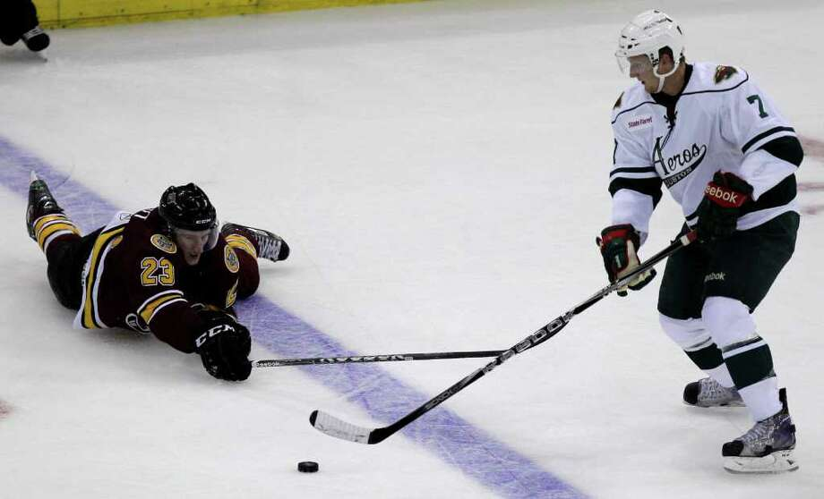 After being tripped, Chicago Wolves Bill Sweatt, left, reaches for the puck against Houston Aeros Kris Fredheim during the third period of AHL game at Toyota Center, Sunday, Oct. 9, 2011, in Houston.   Aeros Carson McMillan received a two minute penalty for tripping Sweatt. Photo: Melissa Phillip, Houston Chronicle / © 2011 Houston Chronicle