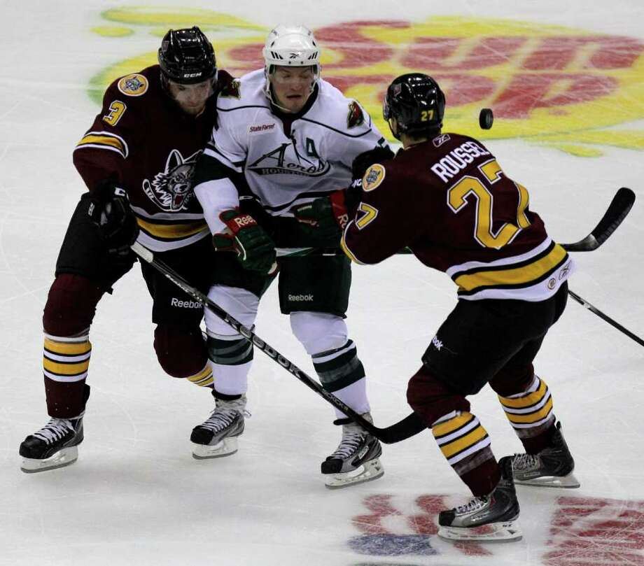 Chicago Wolves (3) Adam Polasek, left, and (27) Antoine Roussel, right, suround Houston Aeros Warren Peters, center, for the puck during the first period of AHL game at Toyota Center, Sunday, Oct. 9, 2011, in Houston. Photo: Melissa Phillip, Houston Chronicle / © 2011 Houston Chronicle