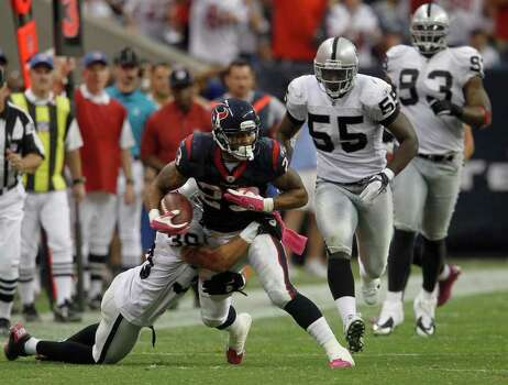 Houston Texans running back Arian Foster (23) is brought down by Oakland Raiders defensive back Jerome Boyd (30) after gaining a few yards in the fourth quarter of an NFL football game at Reliant Stadium, Sunday, Oct. 9, 2011, in Houston. Raiders won the game 25-20. Photo: Karen Warren, Houston Chronicle / © 2011 Houston Chronicle